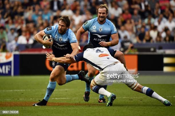 Montpellier's South African centre Francois Steyn runs to evade Castres' French lock Loic Jacquet during the French Top 14 final rugby union match...