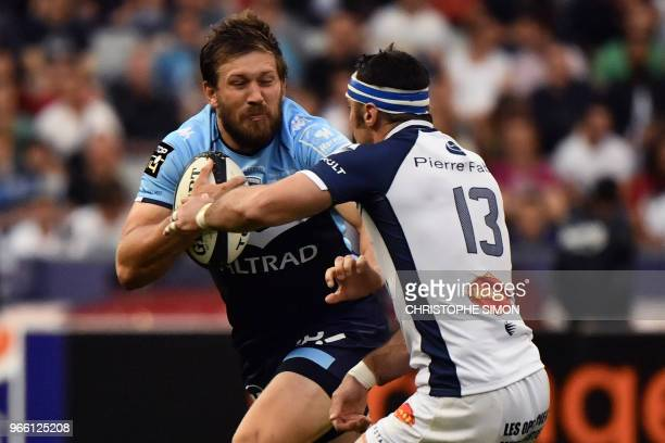 Montpellier's South African centre Francois Steyn runs to evade Castres' French centre Thomas Combezou during the French Top 14 final rugby union...