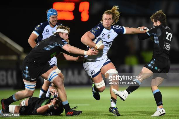 Montpellier's South African lock Jacques Du Plessis is tackled by Glasgow Warriors' Peter Horne and Glasgow Warriors' Scottish lock Jonny Gray during...