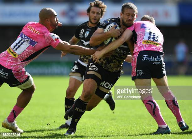 Montpellier's South African number eight François Steyn is tackled by Exeter's winger Olly Woodburn and Exeter's flyhalf Gareth Steenson during the...
