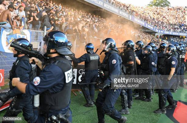 Montpellier's supporters react in front of riot police forces during the French L1 football match between Montpellier and Nimes on September 30 2018...
