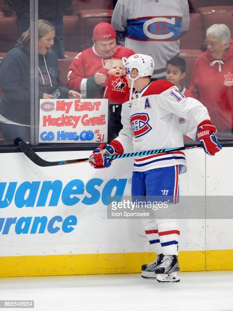Montréal Canadiens rightwing Brendan Gallagher looks at a baby behind the glass during the pre skate before a game against the Anaheim Ducks on...