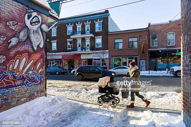 Montréal Québec Canada January 6 2016 A mother is walking with a buggy in St Viateur street