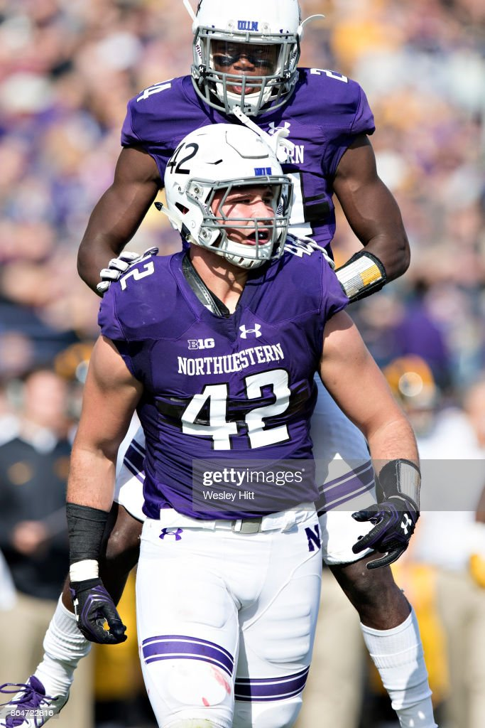 Montre Hartage #24 and Paddy Fisher #42 of the Northwestern Wildcats celebrate after a big tackle during a game against the Iowa Hawkeyes at Ryan Field on October 21, 2017 in Evanston, Illinois. The Wildcats defeated the Hawkeyes 17-10.