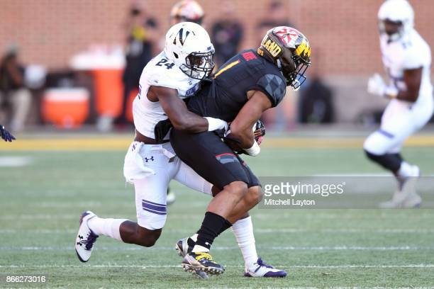 Montre Hartage of the Northwestern Wildcats tackles DJ Moore #1 of the Maryland Terrapins during a college football game at Capitol One Field on...