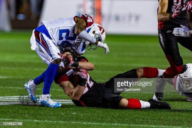 Montreal Alouettes defensive back TJ Heath tackles Ottawa Redblacks wide receiver Greg Ellingson during Canadian Football League action between the...