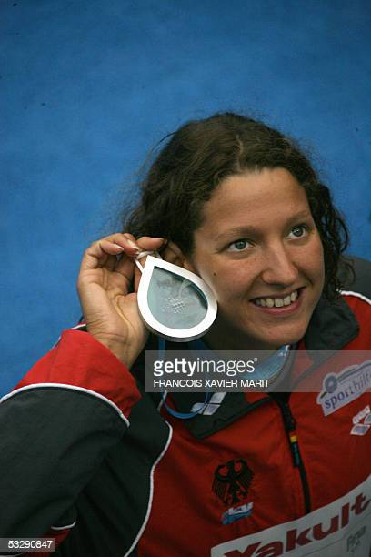 Antje Buschschulte of Germany shows her silver medal following the Women's 100M Backstroke final 26 July 2005 at the XI FINA Swimming World...