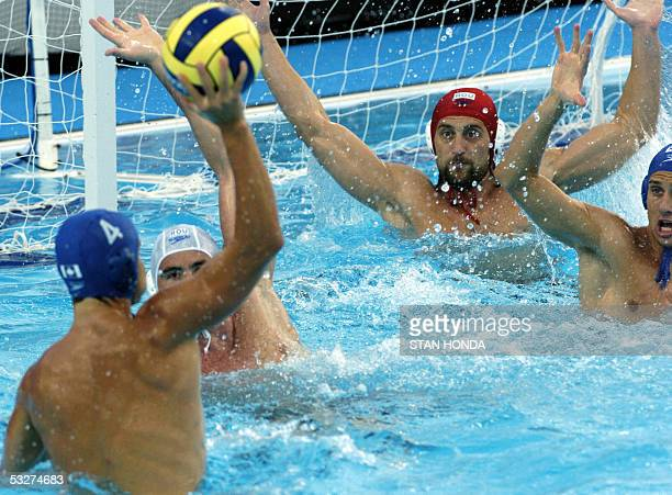 Canada's Kevin Mitchell prepares to pass the ball as several Romanian defenders attempt to block during their Men's preliminary Water Polo match 22...