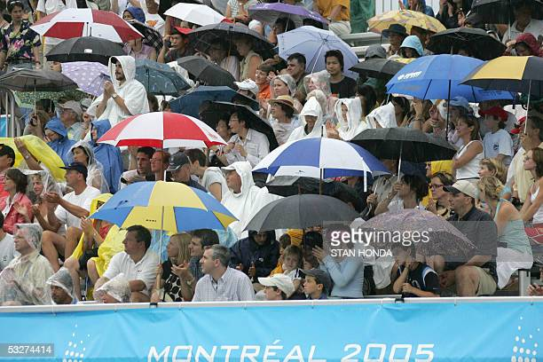 Fans at the diving venue don umbrellas and rain gear during a downpour 22 July 2005 at the XI FINA Swimming World Championships at Parc JeanDrapeau...