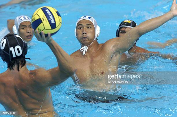 Germany's Lukasz Kieloch prepares to fire the ball at the goal over an unidentified Chinese defender during their Men's preliminary Water Polo match...
