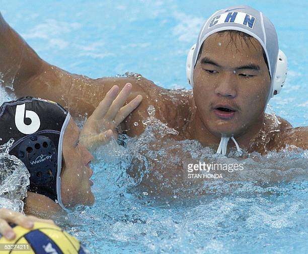 Germany's Marc Politze pushes off an unidentified Chinese defender during action in their Men's preliminary Water Polo match 22 July 2005 at the XI...