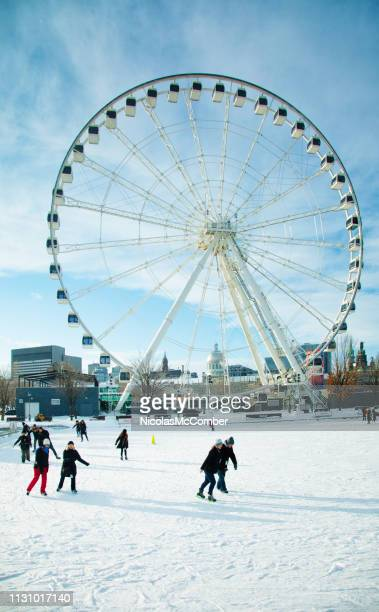 montreal canada people skating under the ferris wheel in old port quarter - montréal stock pictures, royalty-free photos & images