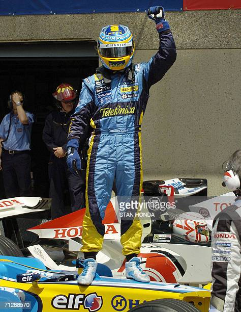 Renault driver Fernando Alonso of Spain stands on his car as he celebrates winning the pole position, 24 June during qualifying for the Formula One...