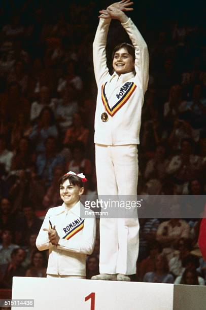 Romanian gymnast Nadia Comaneci is shown waving from the first place position on the winner's podium after she had won gold at the 1976 Montreal...