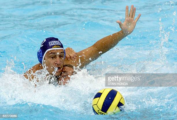Russia's Yury Yatsev comes over the top of Spain's Xavier Valles during their Men's preliminary Water Polo match 22 July 2005 at the XI FINA Swimming...