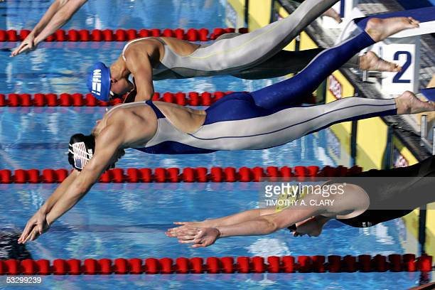 Swimmers dive into the pool at the start of the Women's 100M Freestyle semifinal 28 July 2005 at the XI FINA Swimming World Championships at Parc...