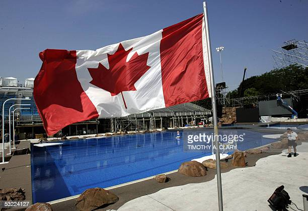 The Canadian flag blows in the wind as workers get opening ceremony props in place at the main competition pool 11 July 2005 in preparation for the...