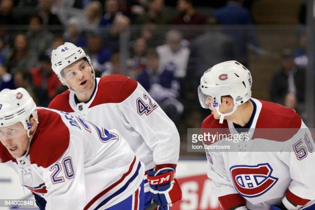 Montreal Canadiens Center Byron Froese talks to teammate Defenceman Noah Juulsen as teammate Left Wing Nicolas Deslauriers readies to take a faceoff...
