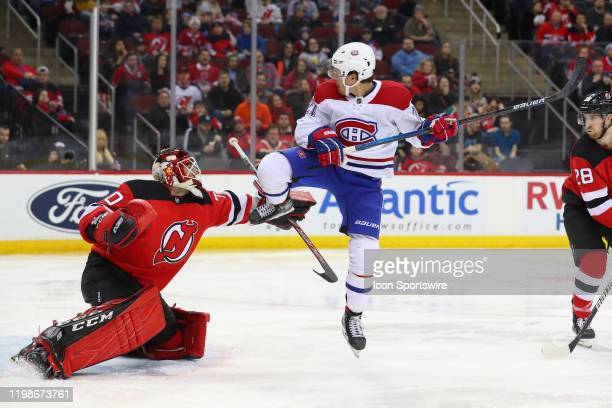 Montreal Canadiens center Nick Cousins jumps in front of New Jersey Devils goaltender Louis Domingue during the third period of the National Hockey...