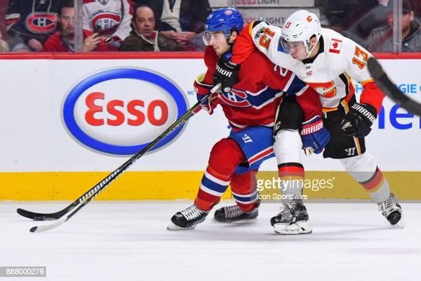 Montreal Canadiens Center Phillip Danault and Calgary Flames Left Wing Johnny Gaudreau battle to keep control of the puck during the Calgary Flames...