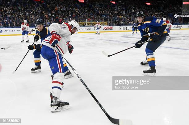 Montreal Canadiens defenseman David Schlemko grabs the puck off of the boards while guarded by St Louis Blues left wing Vladimir Sobotka during an...