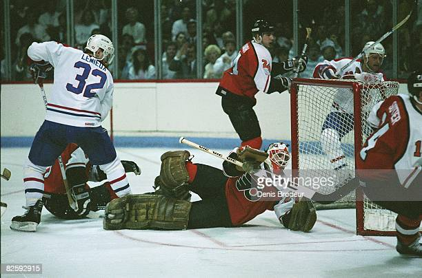 Montreal Canadiens forward Claude Lemieux stands over prone Flyers goaltender Ron Hextall in game action at the Montreal Forum during the Wales...