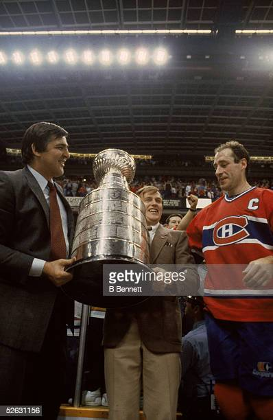 Montreal Canadiens General Manager Serge Savard and team coach Jean Perron celebrate a Stanley Cup victory with team captain Bob Gainey at the Saddle...