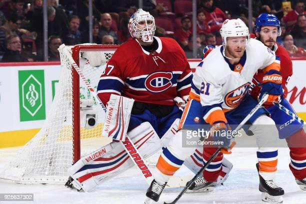 Montreal Canadiens Goalie Antti Niemi looks over New York Islanders Winger Chris Wagner and Montreal Canadiens Defenceman Victor Mete standing in...