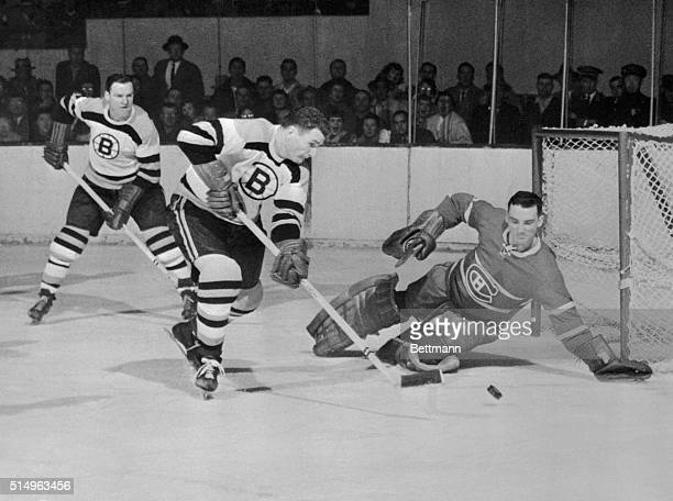Montreal Canadiens goalie Jacques Plante knocks out a shot fired by Boston Bruins player Vic Stasiuk during the first period of a hockey game held at...