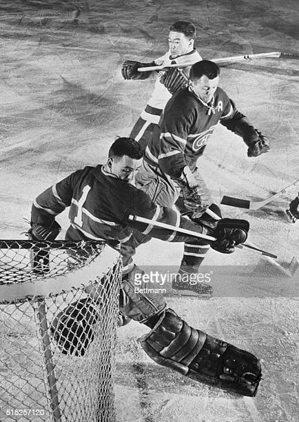 Montreal Canadiens goalie Jacques Plante looks over his shoulder to discover the shot by Marcel Pronovost of the Detroit Red Wings is in the net for...