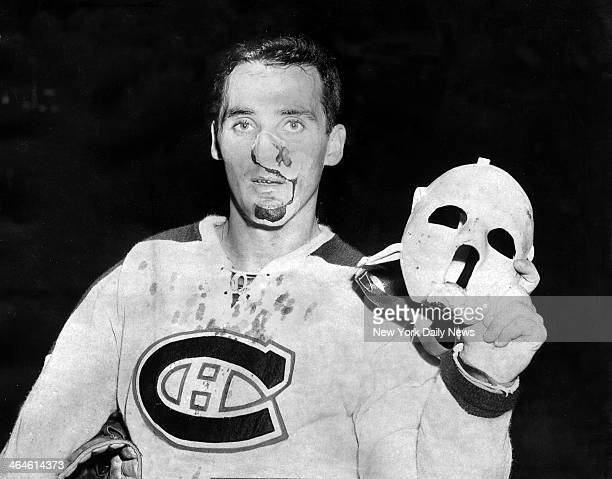 Montreal Canadiens' goalie Jacques Plante shows mask he wore after receiving seven stitches during hockey game with Rangers at Madison Square Garden
