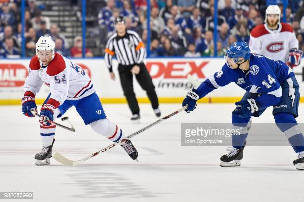 Montreal Canadiens left wing Charles Hudon plays the puck before the stickcheck by Tampa Bay Lightning left wing Chris Kunitz during the third period...