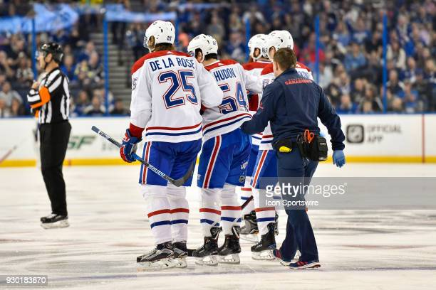 Montreal Canadiens left wing Jacob de la Rose and teammates assist Montreal Canadiens left wing Charles Hudon off the ice during the third period of...