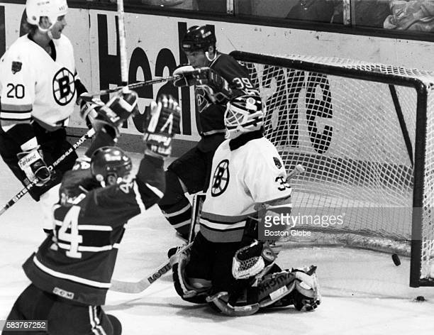 Montreal Canadiens player Stephane Richer front and Brian Skrudland back celebrate a goal while Boston Bruins player Bob Sweeney left and goaltender...
