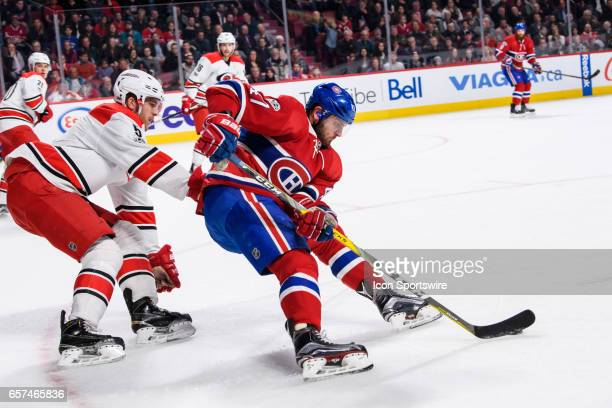 Montreal Canadiens right wing Alexander Radulov skates with the puck while being chased by Carolina Hurricanes defenseman Noah Hanifin during the...