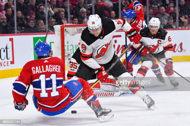 Montreal Canadiens Right Wing Brendan Gallagher falls on the ice while New Jersey Devils Defenceman Steven Santini gains cocntrol of the puck back...
