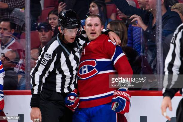 Montreal Canadiens right wing Brendan Gallagher is hold by linesman Steve Barton during the second period of the NHL preseason game between the New...