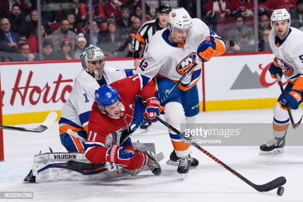 Montreal Canadiens right wing Brendan Gallagher tries to keep control of the puck while falling in front of the net of New York Islanders goaltender...