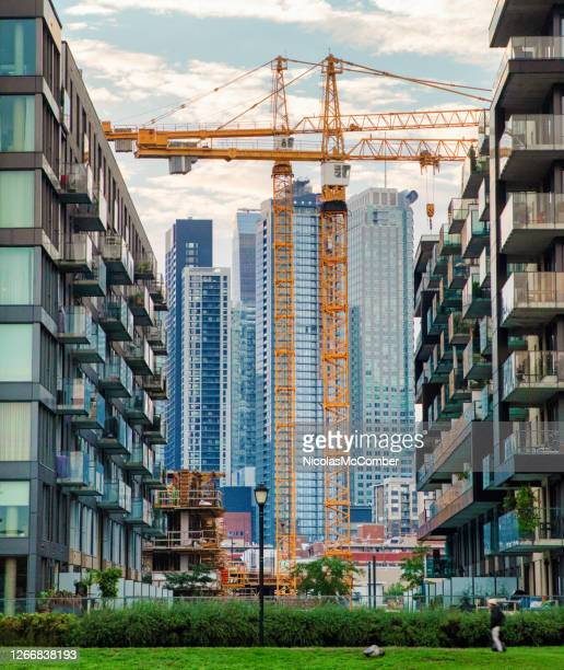 montreal downtown under construction with tower construction equipment between apartment buildings - 20th century style stock pictures, royalty-free photos & images
