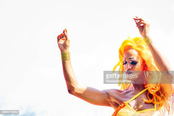 montreal gay pride parade drag queen performer in orange wig dancing - transvestite stock photos and pictures