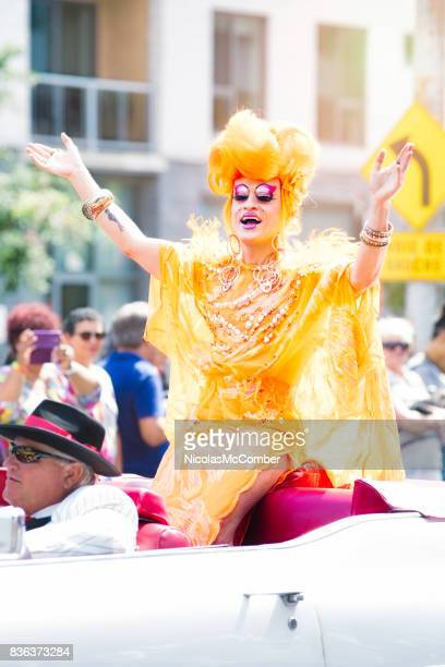 montreal gay pride parade drag queen performer welcoming crowd with open arms - crossdressing party stock photos and pictures