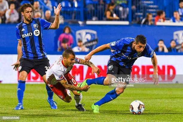 Montreal Impact midfielder Blerim Dzemaili and Toronto FC forward Sebastian Giovinco falling on the ground while battling to control the ball during...