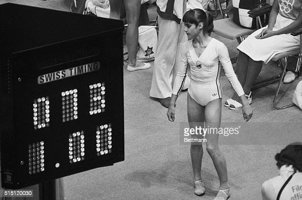 Nadia Comaneci looks at the Olympic scoreboard indicating her perfect score of 100 as 100 because the computer and the display facility were not...