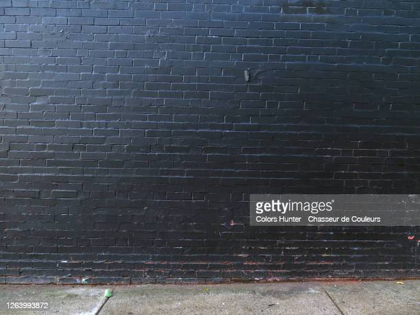 montreal old brick wall painted in black and dirty concrete sidewalk - brick wall stock pictures, royalty-free photos & images