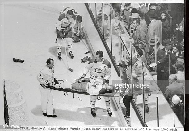 Montreal right winger Bernie BoomBoom Geoffrion is carried off ice here with damaged ribs as first casualty of the National Hockey league season...