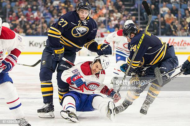 TOPSHOT Montreal's Andrew Shaw is taken down by Buffalo's Derek Grant and Nicolas Deslauriers during the third period of season opener between the...