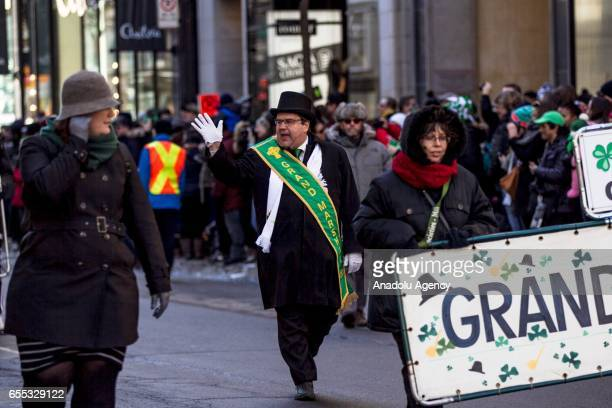 Montreal's mayor Denis Coderre salutes people during the St Patrick parade in downtown Montreal Canada on March 19 2017 Saint Patrick's Day or the...