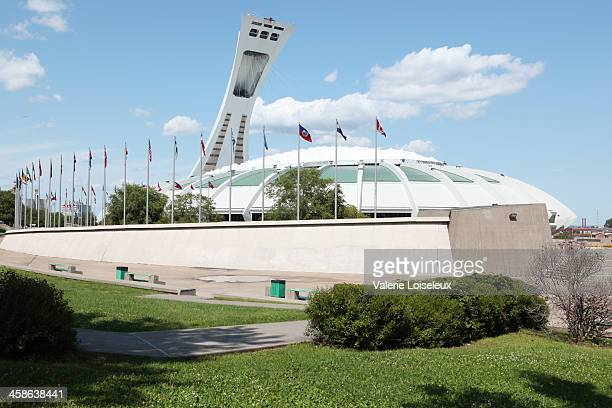 montreal's olympic stadium and international flags - montreal olympic stadium stock photos and pictures