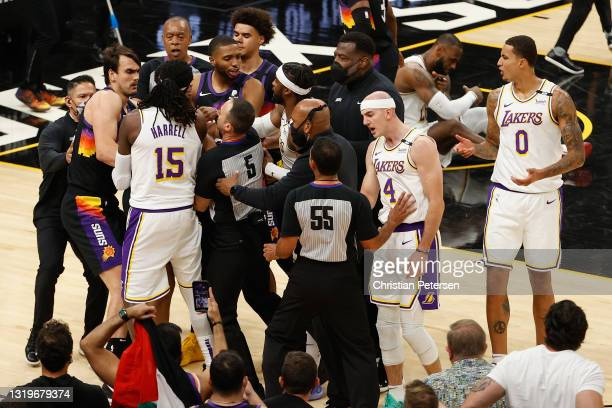 Montrezl Harrell, Alex Caruso and Wesley Matthews of the Los Angeles Lakers come together with Dario Saric, Cameron Payne and Mikal Bridges of the...