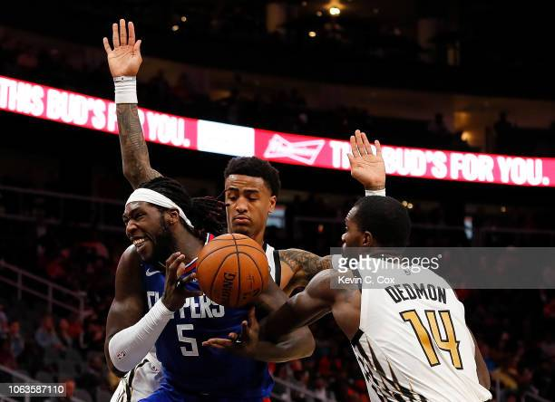 Montrezl Harrell of the LA Clippers draws a foul as he drives against Dewayne Dedmon and John Collins of the Atlanta Hawks at State Farm Arena on...